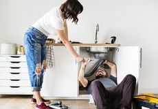 Couple fixing kitchen sink at home royalty free stock images