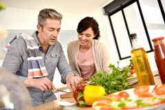 Couple fixing lunch in modern kitchen stock image