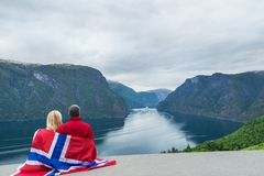 Couple with the flag of Norway looks at the fjord Stock Image