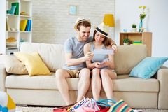 Couple with flight tickets. Happy young couple looking at air tickets while sitting on sofa at home Royalty Free Stock Image