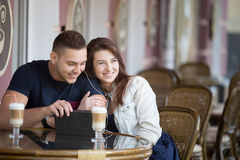 Couple flirting at a cafe. Portrait of beautiful young couple in casual clothes sitting in street cafe in summer sharing earphones, using tablet, looking into Stock Photography