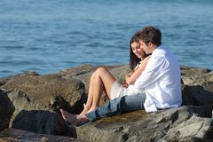 Couple flirting and hugging beside the sea. Couple flirting and hugging sitting on a stone with the sea in the background Stock Photo