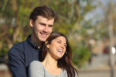 Couple flirting looking away in a park. Happy couple flirting and laughing looking away in a park royalty free stock photo