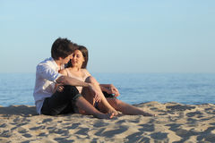 Couple flirting sitting on the sand of the beach. With the sea in the background Stock Image