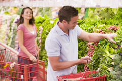 Couple flirting in supermarket aisle Stock Images
