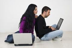 Couple on floor browsing internet on laptops Royalty Free Stock Images