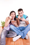 Couple on the floor  eating. Happy smiling young couple sitting on the floor and eating Stock Image