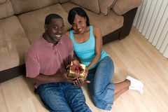 Couple On The Floor Holding A Gift Box-Horizonta Royalty Free Stock Image