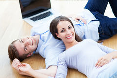 Couple on floor with laptop Stock Image