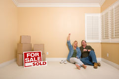 Couple on Floor Near Boxes, Sold Real Estate Signs Stock Images