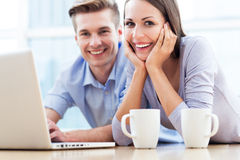 Couple on floor using laptop Stock Images