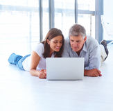 Couple on the floor working on laptop Royalty Free Stock Photos