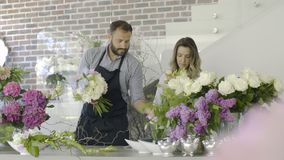 Two young florists working at flowers shop. Couple of floral artists working at flower shop. Handmade and small business concept stock video footage