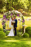 Couple in flower arch. On nature Stock Photos