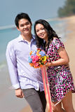 Couple with flower bouquet on the beach Royalty Free Stock Photography