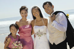 Couple With Flower Bouquet And Bridesmaid On Beach Royalty Free Stock Image