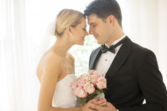Couple With Flower Bouquet Rubbing Noses Royalty Free Stock Photography