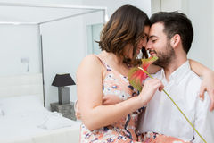 Couple with flower in hotel suite. Close up portrait of men holding women in arms. Couple with red flower in room showing affection Royalty Free Stock Images