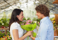 Couple in flower nursery. Mid adult couple in flower nursery holding bouquet and looking each other Stock Images