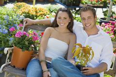 Couple With Flower Plants Sitting On Bench Stock Photography
