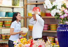 Couple in flower shop. Mid adult couple playing with flowerpots in flower shop Stock Image