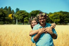 Couple with flowers crowns huging in a field Royalty Free Stock Photography