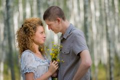 Couple with flowers in love hug in forest Stock Photo