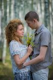 Couple with flowers in love hug in forest Stock Photography