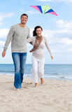 Couple fly kite. Happy outdoor autumn winter spring couple embracing and running on beach a kite fly royalty free stock image