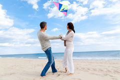Couple fly kite. Happy outdoor autumn winter spring couple embracing and running on beach a kite fly royalty free stock photo
