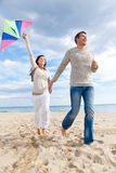 Couple fly kite. Happy outdoor autumn winter spring couple embracing and running on beach  a kite fly Stock Image
