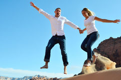 Couple Flying through the air above sand dune Royalty Free Stock Images