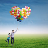 Couple Flying with Balloons Royalty Free Stock Photography