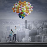 Couple flying with colorful balloons Stock Photo
