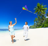 A couple flying a kite on the beach Stock Photography