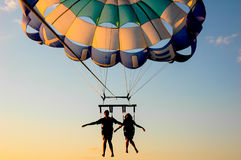 A couple flying on a parachute. A couple flying on a parachute at sunset Royalty Free Stock Photos