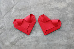 couple folding red paper hearts on cement wall for valentine pat Stock Images