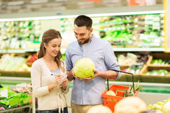 Couple with food basket shopping at grocery store. Shopping, food, sale, consumerism and people concept - happy young couple with basket and notebook buying Royalty Free Stock Photo