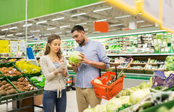 Couple with food basket shopping at grocery store Stock Image