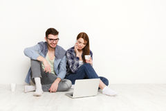 Couple at food delivery web site on laptop, calling on mobile to make an order Stock Images