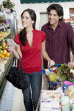 Couple Food Shopping In Supermarket. Smiling young couple with list food shopping in supermarket Royalty Free Stock Photo