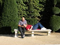 Couple in the forties, tenderly looking at each other on a bench in Paris-Stock Photos. Couple in the forties, tenderly relaxing on a bench in Paris-Stock Photos Stock Images