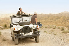 Couple In Four-Wheel-Drive Car In Desert Royalty Free Stock Images