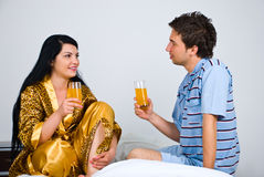 Couple with fresh orange juice on bed in morning Stock Photos