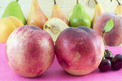 Couple of fresh peaches with fruit arrangement in the background Royalty Free Stock Image