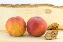 Couple of fresh peaches and kernels  on a natural wooden board Stock Images