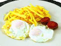 A couple fried eggs. And chips and sausage Royalty Free Stock Images