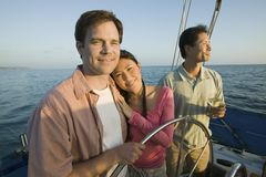 Couple with friend relaxing on yacht Stock Photos