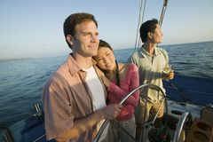 Couple with friend at steering on yacht Royalty Free Stock Photo