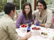 Couple With Friend At Verandah Table Royalty Free Stock Image